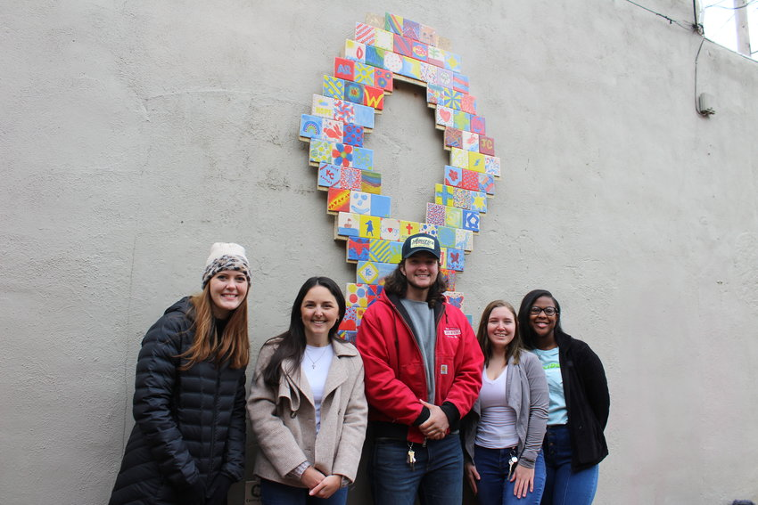 University of Central Missouri students Isabel Anderson, Caitlyn Harrison, Robert (RJ) Appleberry, Sarah Edington and Kevione (Kaye) Scott pose for a photo in front of the mosaic they constructed as part of a class project to assist RISE Community Services.