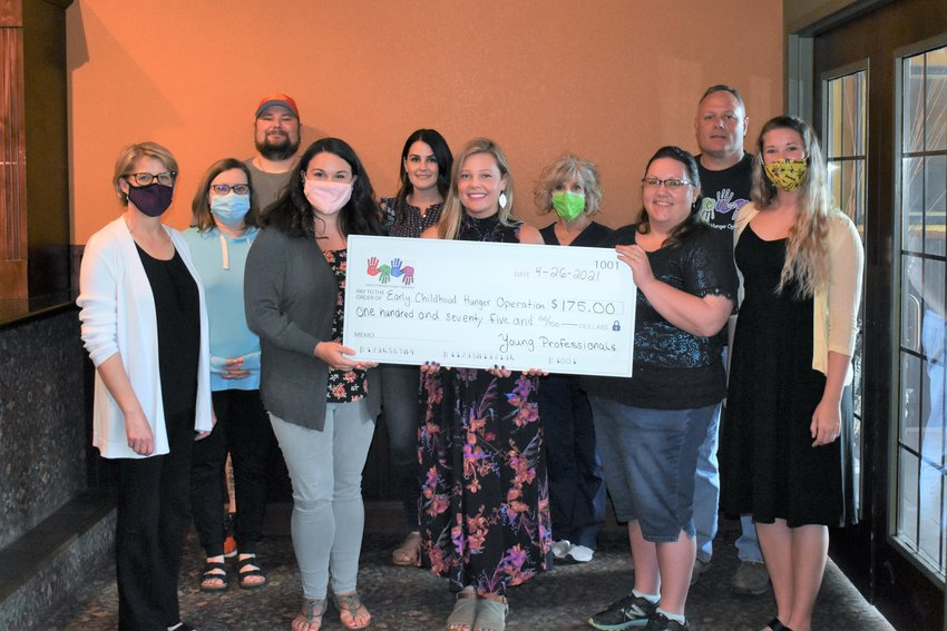 ECHO Executive Director Dawn Moore accepts the Warrensburg Young Professionals' donation alongside ECHO Board member and YP member Andrea Robinson, YP Chair Jamie Brisbin, YP-Chamber Liaison Amanda Flues, Chamber Executive Director Suzanne Taylor and other ECHO Board of Directors members.