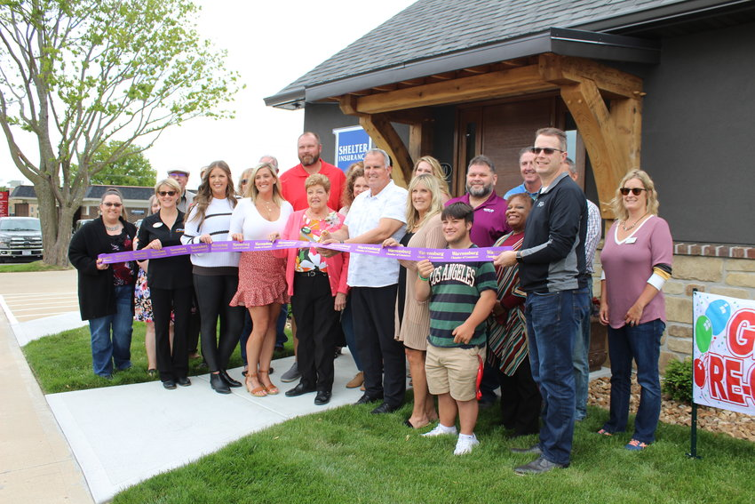 Craig Hibdon prepares to cut the ceremonial ribbon alongside his family, friends and Warrensburg Chamber of Commerce members and staff.