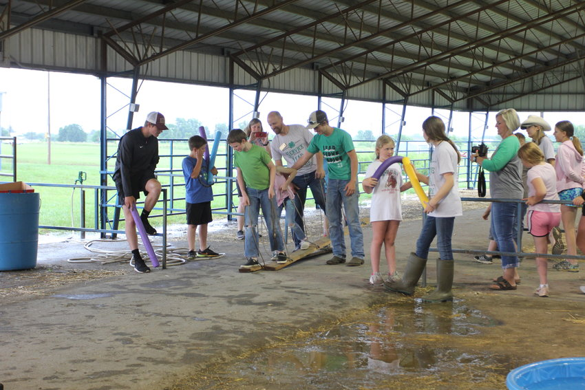 The Farm Time Fun event at the Johnson County Fair was moved under cover due to the rain Saturday, July 10. Kids had to work in a team to complete a series of challenges, including plank walking.