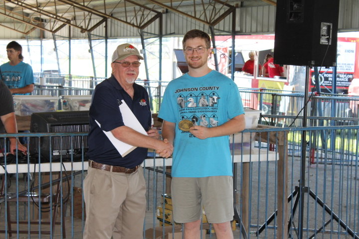 Larry Smith of KMMO presents August Hoeper of the Mt. Moriah Hustlers 4-H Club with the Youth In Agriculture Award.