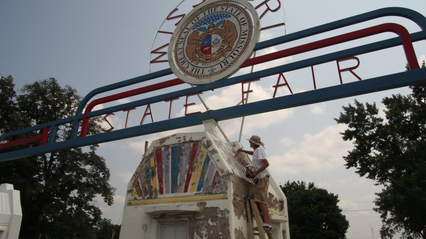Fair employee Jack Hazell paints the entrance sign at the Missouri State Fair in Sedalia on Wednesday.