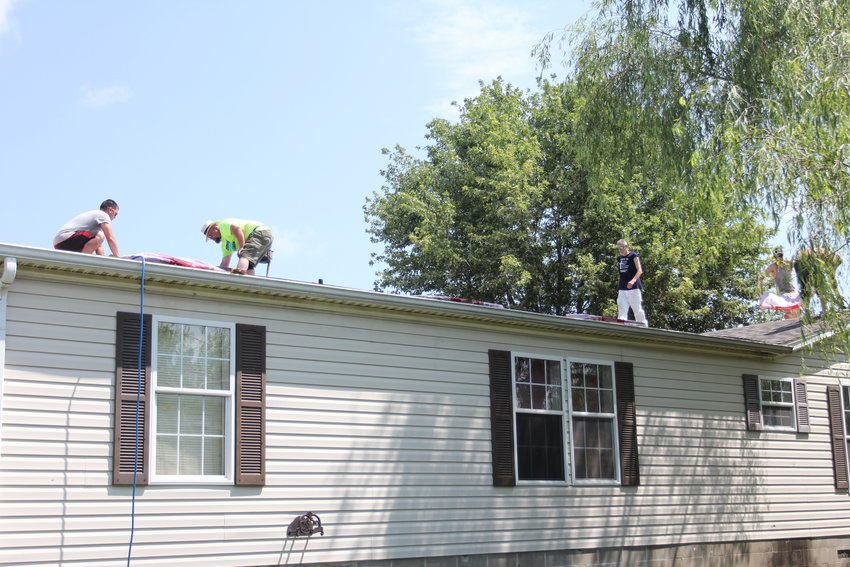 Volunteers for the Fuller Center for Housing lay shingles for a new roof Saturday, July 24, in Knob Noster.