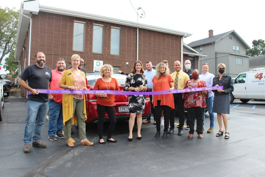 Action Realty Co. real estate agent Chelsea Lee prepares to cut the Warrensburg Chamber of Commerce's ceremonial ribbon on Tuesday, Oct. 5.