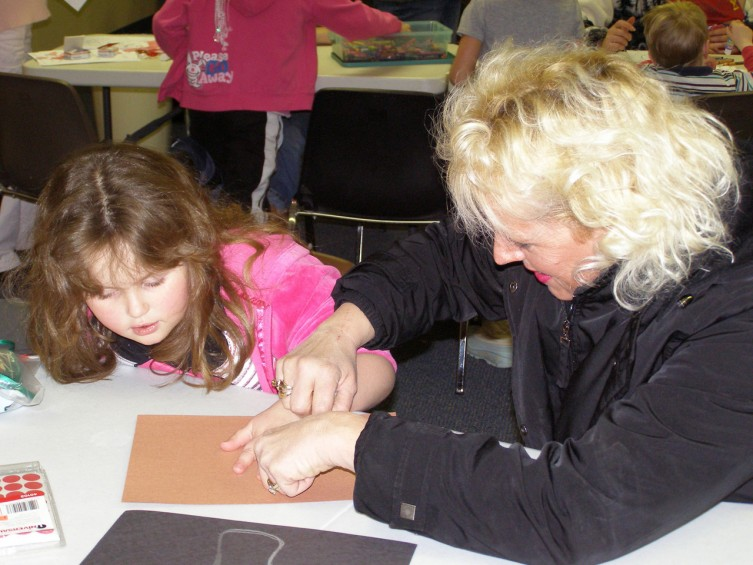Kim Jackson helps her daughter Amanda, 5, trace her hand to make antlers for a cut-out reindeer project.