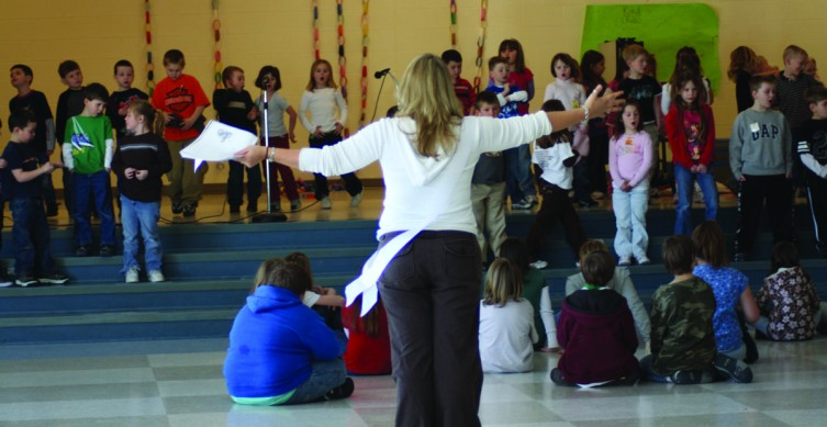 "Mrs. Nuebecker directs kindergarten students at Surline Elementary in a rehearsal of their play ""Friendly Neighborhood Helpers"" while the fourth grade students watch. The kindergarteners each had a part in the play, introducing and singing about 10 neighborhood helpers like the crossing guard, firemen, chefs and the garbage truck men."