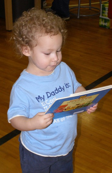 Michael Field, 2, examines the book he earned as a prize at one of the games during the carnival last Friday.