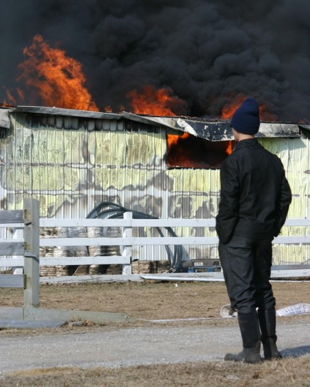 Onlookers watch the blaze as the storage facility behind the Pioneer General Store burns.