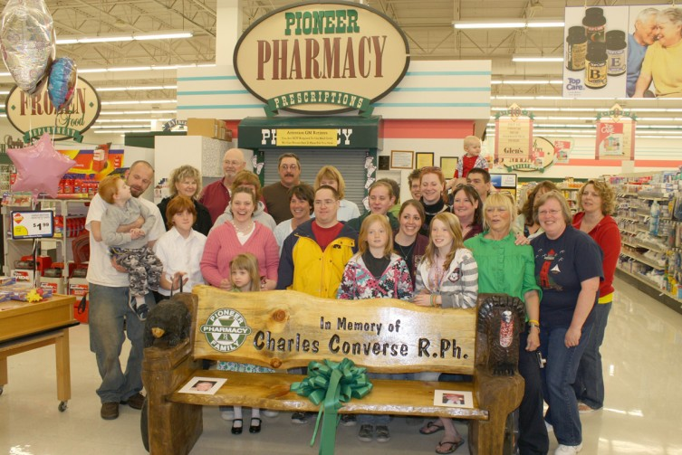 Family and friends of Charles Converse gathered at Glen's Market Saturday to dedicate a bench that was made in his honor. Converse was a partner at Pioneer Family Pharmacy, and owner of Parliament Pharmacy, which merged with Pioneer Family Pharmacy in 1996. Converse died in October 2008. The bench was built by Thee Sign Shop in Roscommon, and the ceremony was held on Converse's birthday, May 2. The bench is currently located inside Glen's Market, in front of the pharmacy where it will remain for the time being until a permanent location can be found.