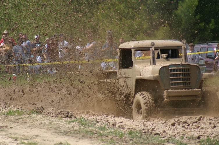 This trucks nice paint job is completely covered while the driver rips through the mud.