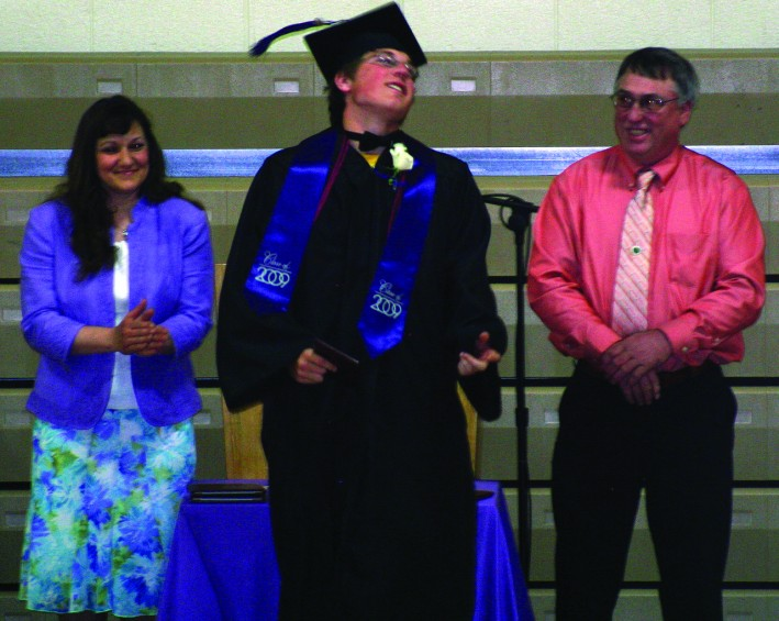 Karl Cooper receives his diploma from school board members Chris Neff and Anne Tompkins.
