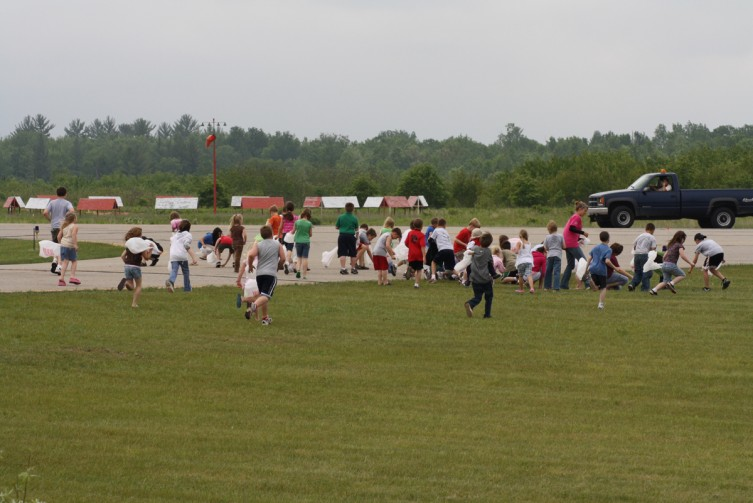 The kids scramble with their bags to pick up as much candy as possible following the candy drop.