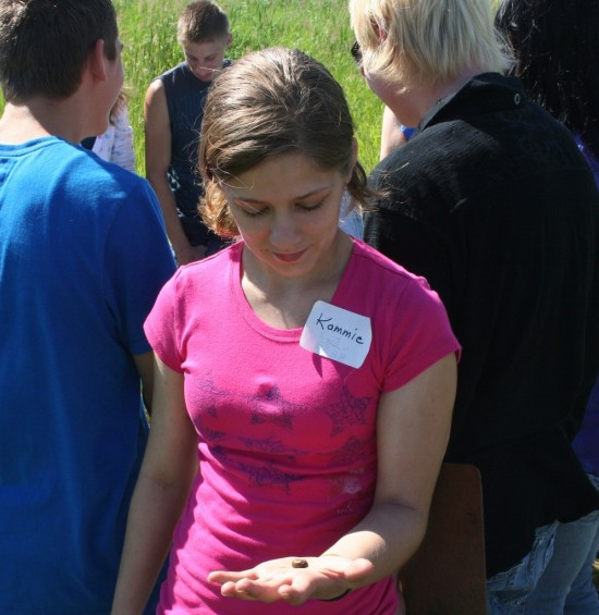 Kammie Steudle, 18, shows a snail that was found at the Pinconning Nature Preserve, part of the Saginaw-Basin Land Conservancy, when a Natural Resources class at the Bay-Arenac Intermediate School District visited the Preserve on June 22.