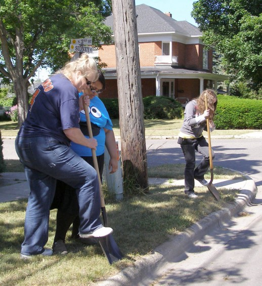 Karen Thomas shows Whitney Fulton to really dig into the grass along the sidewalk, while Kaitlyn Morphy works in her area.