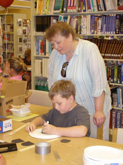 Jude Raifsnider, 7, makes a mask at the craft center in the library while his great-aunt Brenda Hughey looks on.