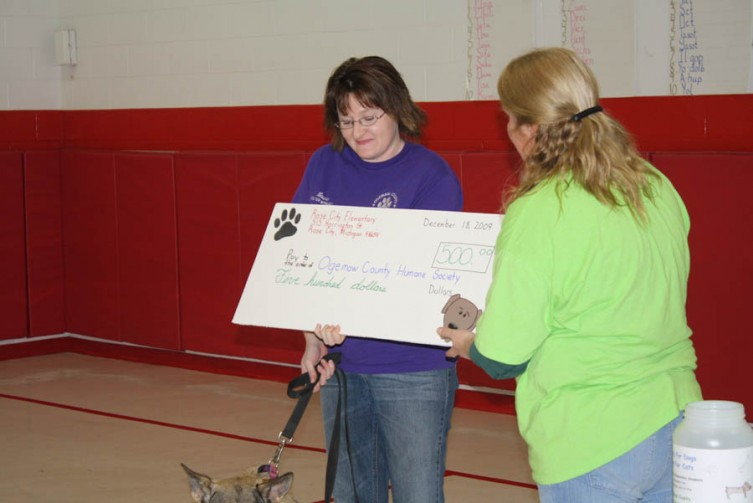 Amy Quigley presents Laura Dean of the Ogemaw County Humane Society with a check for $500 raised during the Dollars for Dogs, Coins for Cats campaign.