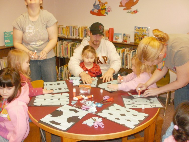 On Tuesday, Jan. 19, the Mio Cooperative Nursery School visited the Oscoda County Library. Students and their parents listened to two stories and then made snowflakes. Pictured, from left, are Madison Van Beest of Mio, Madison Major of Fairview, Lindsay Major (standing), Ember Johnson and dad Chris of Mio, Claire Van Beest of Mio.