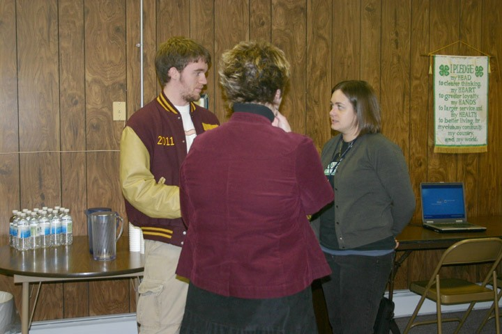 """From left, Fairview resident Jerry Easlick, Allison Weber (an AmeriCorps service member with the Michigan State University Extension's Peer Mentoring Program in both the Mio and Fairview school districts) and Donita Charron, the new office manager at the Oscoda County MSU Extension, chat during a """"Treat & Great"""" gathering Thursday, Jan. 28 at the Oscoda County MSU Extension office in Mio."""