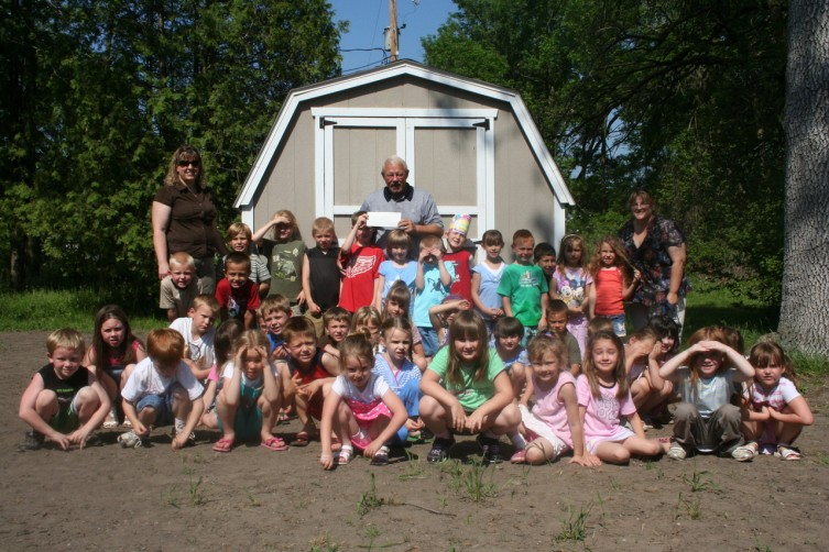 Members of Mrs. Morel (left), and Ms. Forro's (right) kindergarten class present Arenac County Habitat for Humanity's Tom McCoy (center) with a check for $110 dollars. The student raised all of the money to help with a storage shed at 333 N. Grove Street in Standish. Berthiaume's Collision transported the shed to the location, while Sequin Lumber sold it to the group for a discounted price of $500.