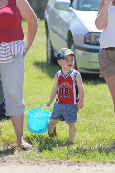 Wyatt Irwin, 2, of Whittemore waits patiently for the parade to begin with his candy bucket in hand.