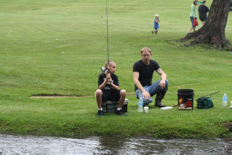 Trevor Likavec, 9, of West Branch gets some advice from his uncle, Rodney, before the start of the fishing derby.
