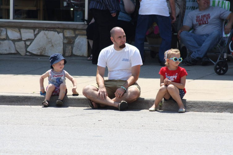 Jonas Benson, 2, and his sister Aubrey Benson, 5, of Flint, wait patiently for the parade to begin with their uncle Andrew Benson.