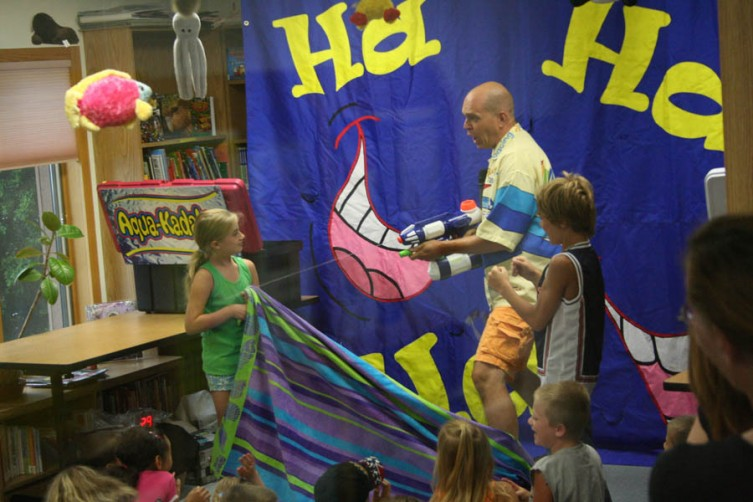 Kids of all ages watch Doug Scheer perform his Aqua-Kadabra Family Fun Show at the Mary Johnston Library in Standish on Thursday. The library was packed with children and adults as Scheer filled the library with laughs and smiles all around.