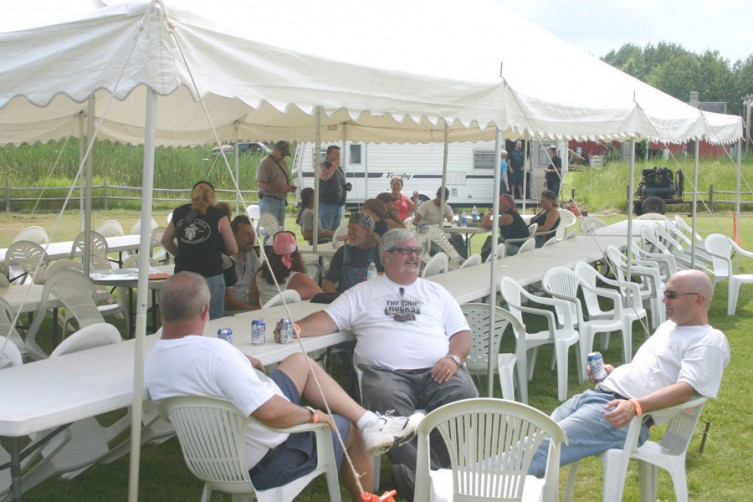 Several guests at the rodeo and pig roast attempt to beat the heat July 10 as they gather underneath a tent.