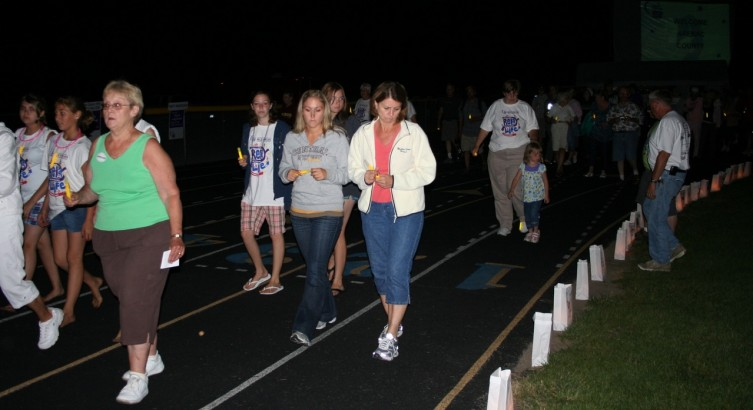Arenac County Relay for Life participants solemnly take the luminaria lap, with glow sticks in hand.