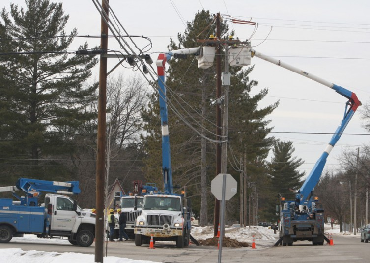 Consumers Energy trucks line the corner of 10th Street and M-33 in Mio on Tuesday, Feb. 15, as employees work to fix electrical lines.