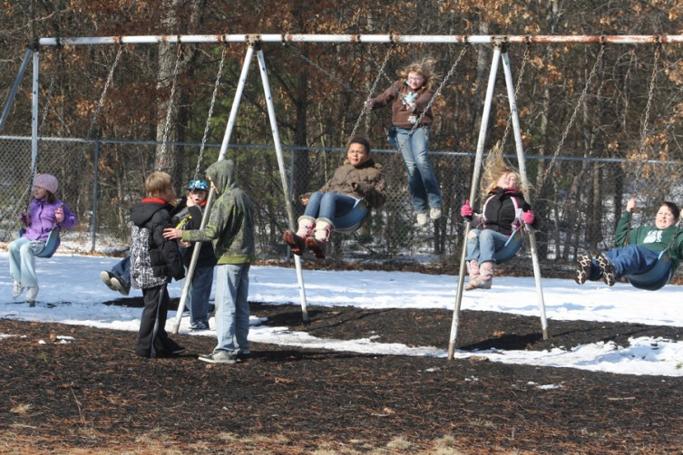A group of students get into the swing of things at Mio AuSable's playground Feb. 24.