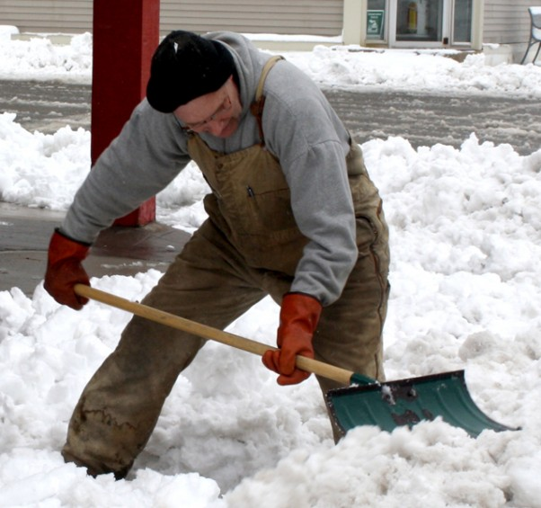 David Gardulski, whose wife, Sharon, owns the Strawberry Patch Resale Shop in Mio, shovels some snow in front of the shop Wednesday, April 20.