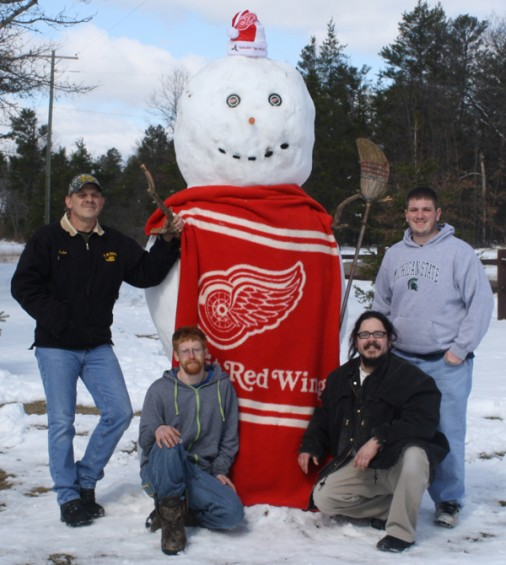 Mio residents (front, l-r) Ty Gerow, Paul Vargas; (back, l-r) John Davis, and Ryan Kalbfleisch stand with a snowman dressed up in Red Wings gear, which they built on Wednesday, April 20, at Davis' Mio home. Vargas said the four residents took about three hours to build the snowman.