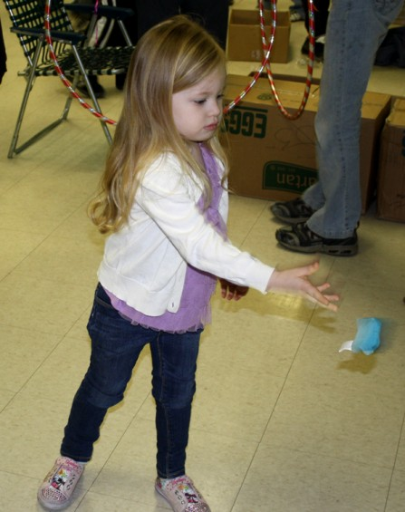 Ava Kirschweng, 4, of Mio, tosses a beanie bag during one of the activities at the party.