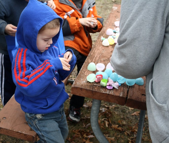 Preston Burgess, 3, of Flushing, sorts through his Easter eggs after the hunt is completed.