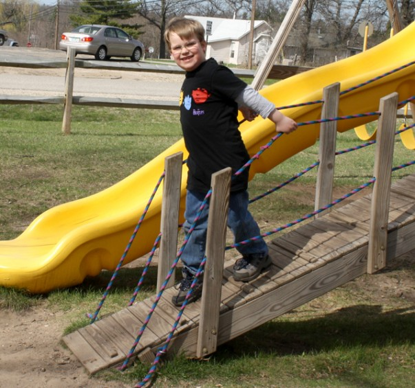 Roch DuPuis, 6, of Mio, makes his way down a ramp at the playground.