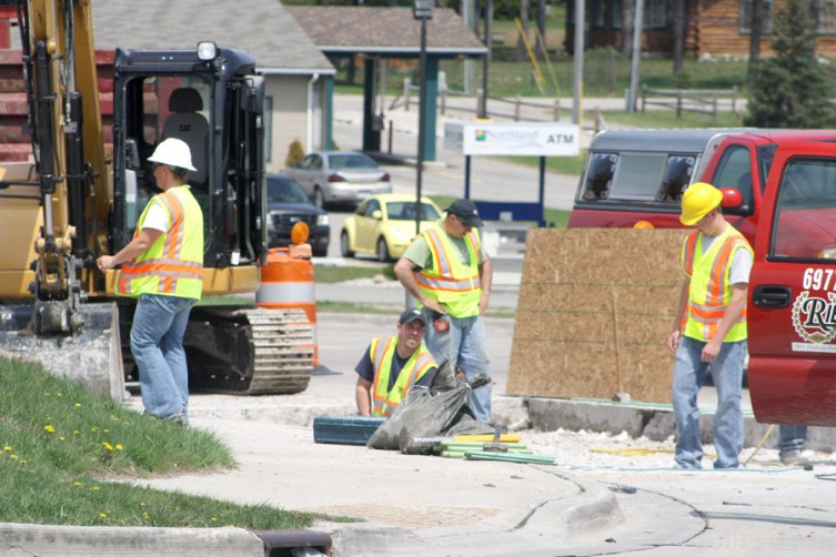 A group of workers repair a section of southbound M-33 on Thursday, May 12.