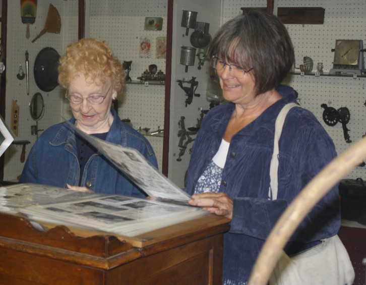 Bette Hardy, at left, of Mio, and Candy Wagner, of Swartz Creek, look through a scrapbook at the museum.