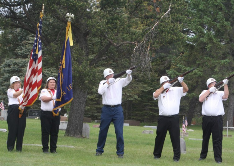 Members of the Rifle Squad of the American Legion Post No. 162 in Luzerne perform a 21-gun salute, as members of the post's Color Guard stand at attention.