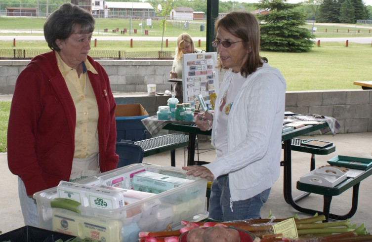 Laura Langenburg of Luzerne, at right, checks out some eggs at the market from vendor Denise Agius of Fairview.