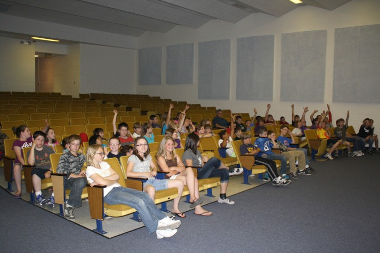 Several Mio Elementary students in the studio audience raise their hands, ready to answer a question.