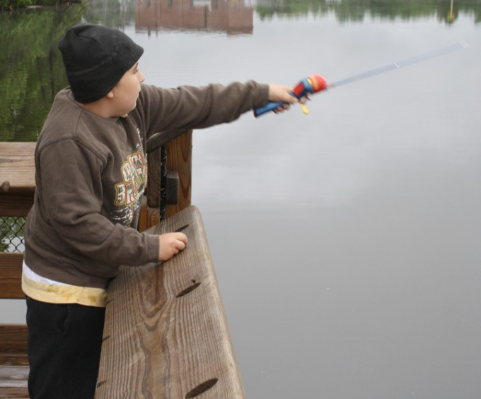 Ben Shackleford, 9, of Mio, casts his line into the AuSable River.
