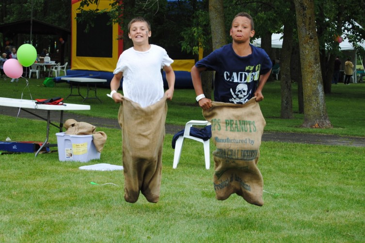 "Leaping through the air, Jesse Smith, 12, and Kenny Moore, 10, both of Standish race to the finish line in their potato and peanut sacks. ""That was awesome,"" said Smith after the race. The Caring Bear Picnic had plenty to keep kids hopping during the June 16 event."