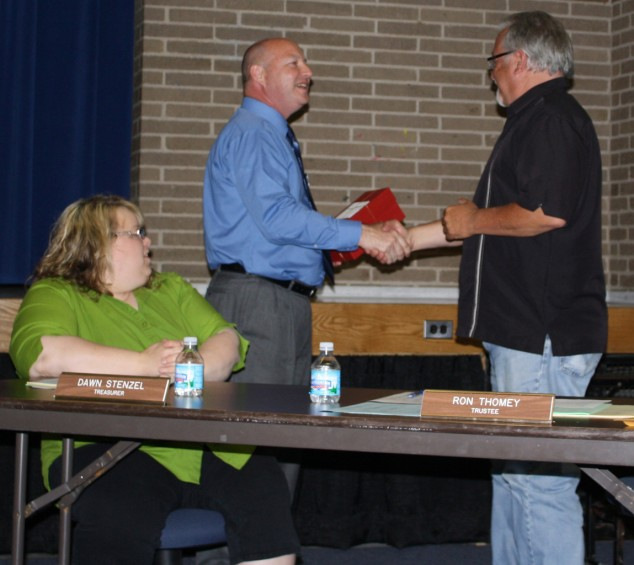 Mio AuSable Schools Superintendent Gary Wood, at left, presents Trustee Ron Thomey with a school bell award as Treasurer Dawn Stenzel looks on.