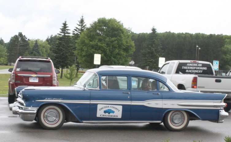 A group of people leave the AuSable Valley parking lot to take a ride in this 1957 Pontiac Star Chief.