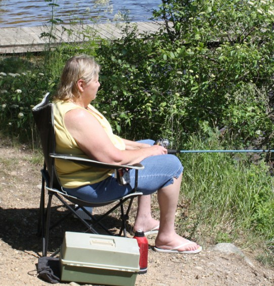 Debbie Palmer of Luzerne checks to see if anything is biting as she fishes at the Mio Pond.