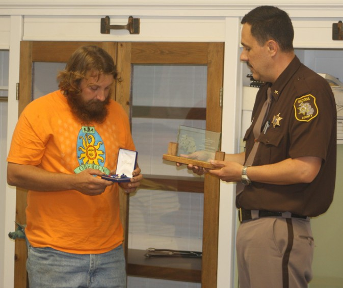 Oscoda County Sheriff Kevin Grace, at right, presents Mio resident Martin McGregor with the Michigan Sheriffs' Association's Citizen's Medal of Valor at the June 28 meeting of the Oscoda County Board of Commissioners.