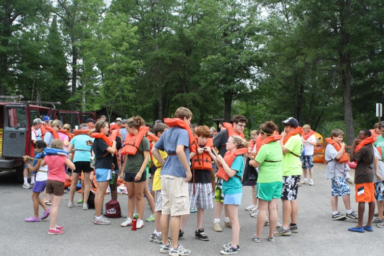 Children attending Mich-lu-ca Camp in Comins make sure their safety vests are secure at the AuSable River public access site in Mio Wednesday, July 27, as they prepare to take a canoe trip to Comins Flats.