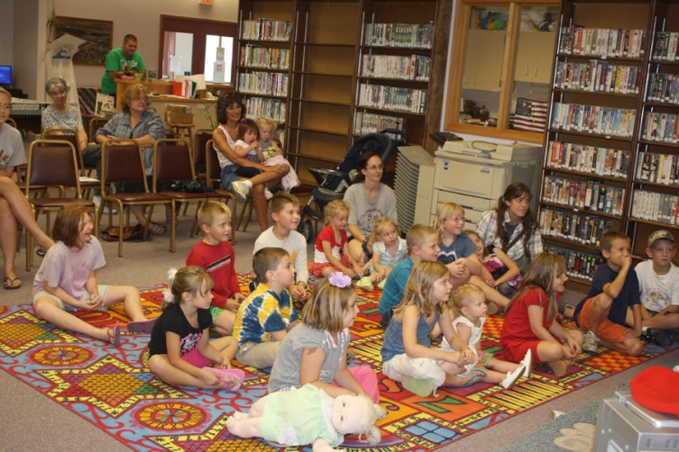 A mixture of children and adults watch a performance by the Acting Up Theatre Company, based in Grayling, at the Oscoda County Library in Mio on Thursday, July 28.