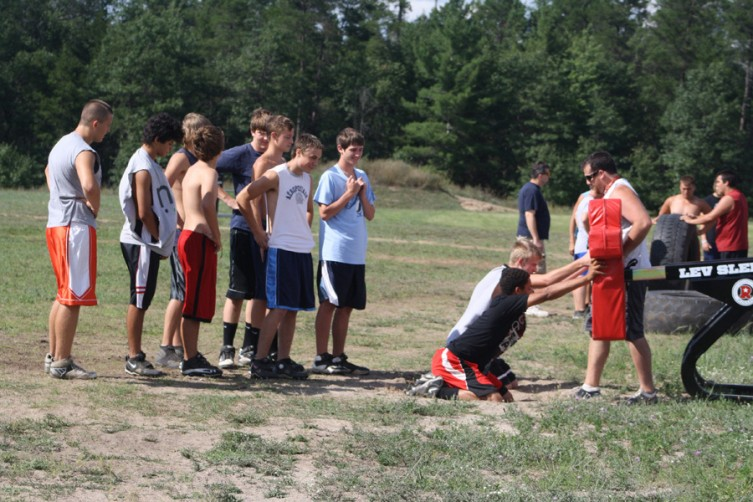 Mio's varsity football team hits the blocking sleds during practice.